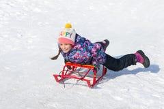 Gelukkig glimlachend meisje op een slee die onderaan een heuvel op sneeuw glijden royalty-vrije stock afbeeldingen