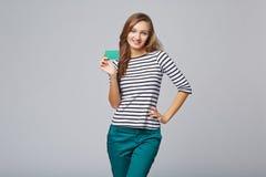 Gelukkig glimlachend meisje in toevallige kleding, die lege creditcard tonen Stock Foto