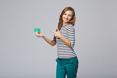 Gelukkig glimlachend meisje in toevallige kleding, die lege creditcard tonen Stock Foto's