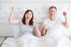 Gelukkig glimlachend middenleeftijdspaar in bed in t-shirt Gezonde familieverhoudingen De ruimte van het exemplaar stock afbeelding