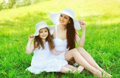 Gelukkig glimlachend moeder en dochterkind die witte strohoeden dragen stock foto's