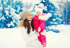 Gelukkig glimlachend moeder en kind die in de sneeuwwinter lopen Royalty-vrije Stock Foto