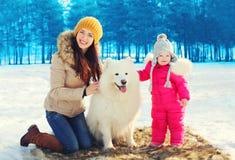 Gelukkig glimlachend moeder en kind met witte Samoyed-hond in de winter Stock Afbeeldingen