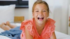 Gelukkig glimlachend mooi meisje die op bed thuis liggen stock videobeelden
