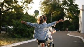 Gelukkig, glimlachend paar die elektrofiets in het park berijden Meisje met uitgestrekte handen Plezier, die in openlucht in hang stock videobeelden