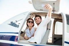 Gelukkig glimlachend paar die selfie de cabine van het binnenkantvliegtuig maken Royalty-vrije Stock Foto's