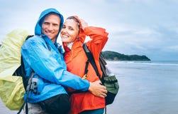 Gelukkig glimlachend reizigerspaar in regenachtige dag op het oceaanstrand stock afbeelding