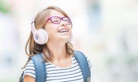 Gelukkig glimlachend schoolmeisje met tandsteunen en glazen het luisteren muziek van hoofdtelefoons Orthodontist en tandartsconce royalty-vrije stock fotografie