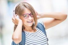 Gelukkig glimlachend schoolmeisje met tandsteunen en glazen het luisteren muziek van hoofdtelefoons Orthodontist en tandartsconce stock fotografie