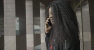 Gelukkig glimlachend vrij het jonge Afrikaanse meisje spreken via de mobiele telefoon en het lachen Openlucht plaats 4k lengte stock videobeelden
