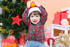 Gelukkig glimlachend weinig jongen in Kerstmanhoed met mandarijn Royalty-vrije Stock Foto's