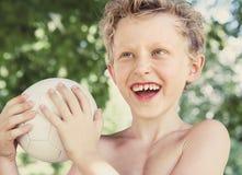 Gelukkig glimlachend weinig portret van de jongenszomer met een bal stock fotografie