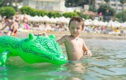 Gelukkig glimlachend weinig spel van de jongenslooppas met golven op strand Italië De zomer royalty-vrije stock fotografie