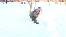 Gelukkig graaft weinig jongen schopsneeuw bij de winter zonnige dag stock video