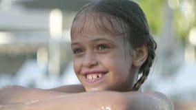 Gelukkig grappig meisje die in gele zonnebril in de camera kijken die, kijkend uit de pool, die op de rand houden glimlachen stock video