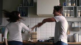Gelukkig grappig romantisch paar die aan muziek in de keuken dansen stock footage