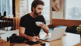 Gelukkig Guy Drinks Coffee While Working op Laptop stock afbeelding