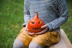 Gelukkig Halloween De meisjeszetels op houten stoel en houdt in openlucht weinig pompoenjack O Lantaarns stock afbeeldingen