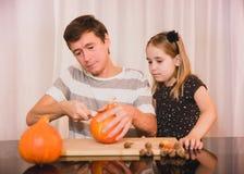 Gelukkig Halloween Dochter en vader snijdende pompoen voor Halloween stock foto