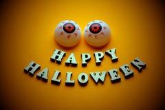 Gelukkig Halloween Een vrolijk gezicht met emotie van houten brieven en twee ballen van oog op een heldere oranje achtergrond Mal stock fotografie