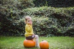 Gelukkig Halloween Het leuke meisje zit op een pompoen en houdt een appel in haar hand stock fotografie