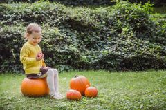 Gelukkig Halloween Het leuke meisje zit op een pompoen en houdt een appel in haar hand stock foto's
