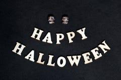 Gelukkig Halloween - inschrijving op een zwarte achtergrond Houten woorden en twee schedels voor decoratie op de dag van alle hei royalty-vrije stock foto's