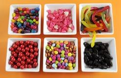 Gelukkig Halloween-suikergoed in vierkante witte kommen Royalty-vrije Stock Foto