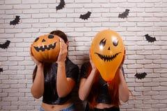 Gelukkig Halloween! Twee jonge leuke vrouwen die met pompoenhoofd partying royalty-vrije stock afbeeldingen