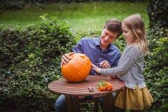 Gelukkig Halloween Vader en dochter snijdende pompoen voor Halloween buiten stock foto's