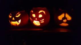 Gelukkig Halloween, zit een familie van pompoenen in een keukenbovenkant die in dark gloeien stock fotografie