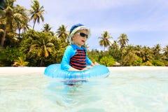 Gelukkig heeft weinig jongen met het levensring pret op strand Stock Foto's