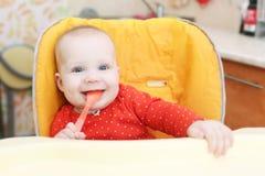 Gelukkig heeft weinig 6 van het babymaanden meisje met lepel diner Stock Foto