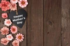 Gelukkig het bordhart van de Moedersdag met bloem zijgrens op hout stock foto's