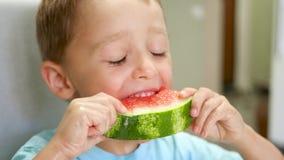 Gelukkig het lachen kindclose-up Een leuke kleine jongen zit bij een lijst en eet een sappige watermeloen met eetlust Kinderen `  stock videobeelden
