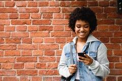 Gelukkig hipstermeisje die haar smartphone bekijken Royalty-vrije Stock Afbeelding