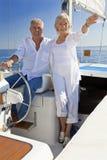 Gelukkig Hoger Paar bij het Wiel van een Boot van het Zeil Stock Afbeelding