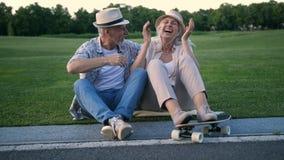 Gelukkig hoger paar die na het met een skateboard rijden lachen stock footage