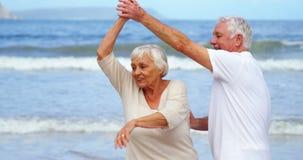 Gelukkig hoger paar die op het strand dansen stock videobeelden