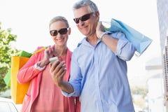 Gelukkig hoger paar die smartphoneholding het winkelen zakken bekijken Stock Foto's
