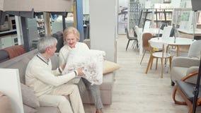 Gelukkig hoger paar die voor meubilair en kussens bij warenhuis winkelen stock footage