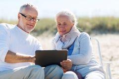 Gelukkig hoger paar met tabletpc op de zomerstrand Stock Foto's