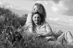 Gelukkig houdend van aantrekkelijk paar die door vuur leggen die in gras en wolken koesteren Het paar houdt van picknick buiten s royalty-vrije stock afbeelding