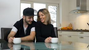 Gelukkig houdend van en paar dat terwijl thuis het drinken van koffie in hun keuken plaagt gekscheert stock video