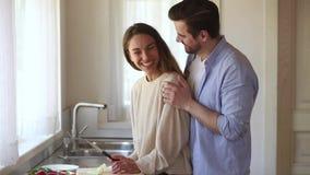 Gelukkig houdend van jong paar die pret hebben die gezonde maaltijd samen voorbereiden stock videobeelden