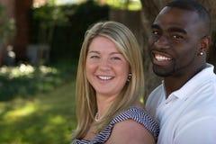 Gelukkig houdend van multicultureel en paar die koesteren glimlachen stock afbeelding