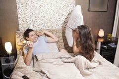Gelukkig houdend van paar die een hoofdkussenstrijd hebben stock afbeelding