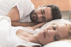Gelukkig houdend van paar die in slaapkamer dutten stock foto