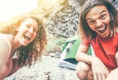 Gelukkig houdend van paar van trekkers die en een selfie maken die mobiele smartphonecamera met behulp van - Jongeren die kamp va stock foto's