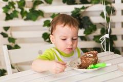 Gelukkig houdt weinig jong geitjejongen die zijn verjaardag vieren stuk van cake, binnen De partij van de verjaardag voor kindere Stock Afbeeldingen